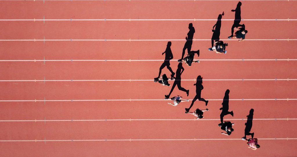 sportivi care alearga pe pista